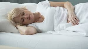 happy middle aged female sleeping in bed on orthopedic mattress