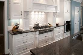 white kitchen cabinets with black quartz the blue wall with the white cabinets grey