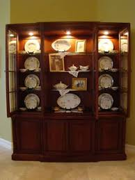 how to decorate your china cabinet add softness to china cabinet with lace napkins and family photos