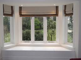 roman blinds in a bay delectable window and curtains windows