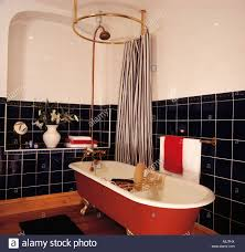striped shower curtain on circular rail above red freestanding
