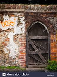 arched old wooden gate door in garden wall stock photo royalty