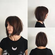 sliced layered chin lengt bob with bangs women s rich brunette soft layered bob with curtain bangs and undone