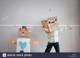 Homemade Toy Box by Boy With Box Covering Head And Homemade Toy Robot Stock Photo