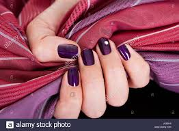 woman with beautiful purple nails gripping a color matched maroon