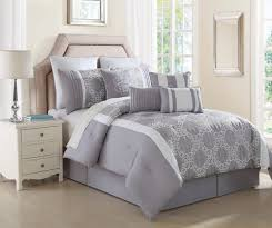 white stained bed side table with three drawer and rounded bedroom cream upholstered bed with white and grey bedding added