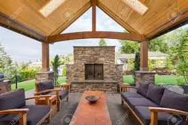 covered patio outside luxury home with large stone fireplace