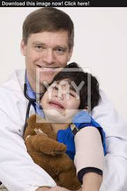 Doctor Comforting Patient Male Doctor Comforting Disabled Toddler Patient On Lap Image
