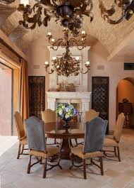 tuscan style dining room with double chandeliers and curved brick
