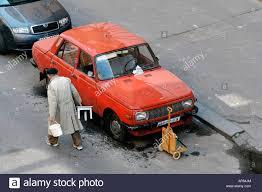 wartburg old man washing old east german car wartburg on the street stock