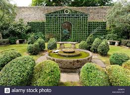 trellis with boxed hedges and water feature in an english garden