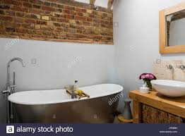 Exposed Brick Wall by Freestanding Bath In Rustic Bathroom With Exposed Brick Wall The