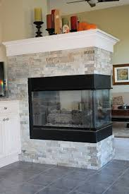 3 sided stone fireplace with wood mantle in this ldk lower level