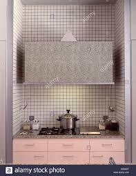 modern pink kitchen closeup of hob in pink kitchen unit below grey storage cupboard in