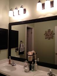 rectangle black framed mirror for bathroom under down light