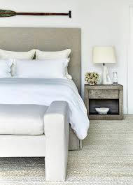 taupe linen headboard with gray bench at foot of bed