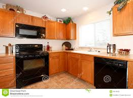 light brown kitchen cabinets with black appliances brown kitchen cabinets with black appliances stock photo