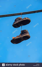 shoes hanging on a wire with blue sky stock photo royalty free shoes hanging on a wire with blue sky