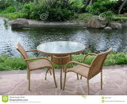 Glass Top Patio Table And Chairs Table And Two Chairs On An Outside Patio By A Pond Stock Photo