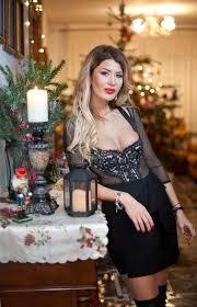 beautiful woman in elegant black dress with xmas tree in