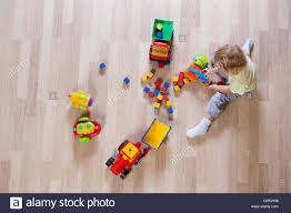 kid play car little blond kid boy playing with colorful car toys on floor top
