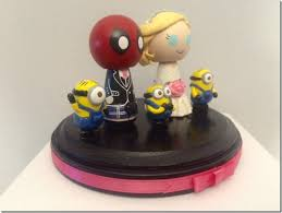 deadpool meets the minions on this great wedding cake topper
