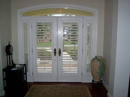 interior view of plantation shutters on a glass front door the