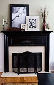 black mantel decor with framed pictures and vase and candle holder