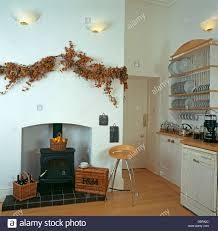 dried flower garland above simple fireplace with wood burning