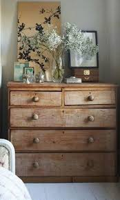 rustic wooden bedroom dresser design with a glass vase of white