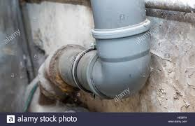 sewer pipes in home basement system of gray sanitary pipes in old