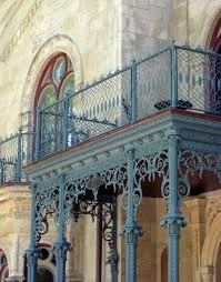 restored ornamental wrought iron mesh balcony railing above the