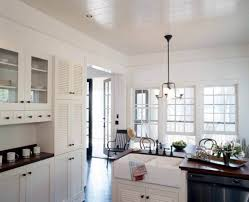 louvered cabinet doors in the kitchen in white color with apron