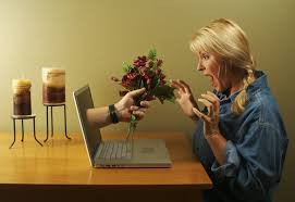 Man     s hand appearing from a laptop with flowers in it  Woman looking shocked at the