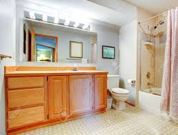 bathroom with wooden vanity bath tub with tile wall trim and