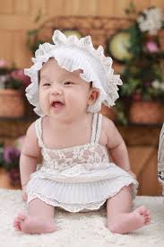 baby in white dress with white headdress free stock photo