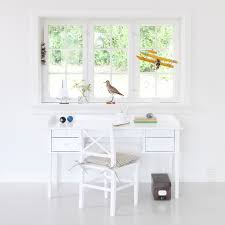 a white desk placed under a window with a traditional cross back chair children s desk