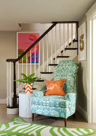 basement staircase with aqua chair and green zebra pillow