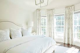 white and ivory bedroom with bay window transitional bedroom