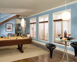 decorating blue wall with white window and white faux wood blinds
