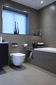 bathroom with grey tiles and drop in tub also tankless toilet