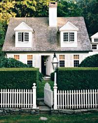 country cottage style house with boxwood and picket fences