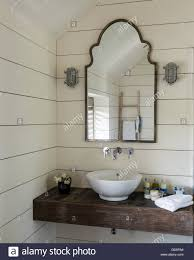 basin resting on slab of timber in bathroom with walls lined white