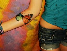 colorful monarch butterfly tattoo on right forearm