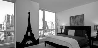 bedroom a painting of the eiffel tower to the left in a bedroom