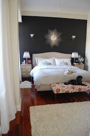 this accent wall is painted a dark grey with white furniture to be