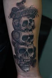 stacked skulls with banner by rafael marte tattoos