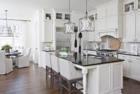 white kitchen island with black countertop and gray curved arm