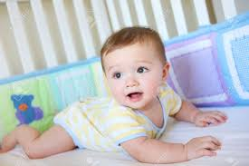 a baby boy in a crib smiling stock photo picture and