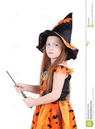 in orange costume of witch for halloween holds wand royalty